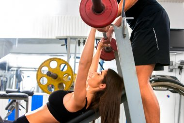 Woman working his arms and chest at gym.