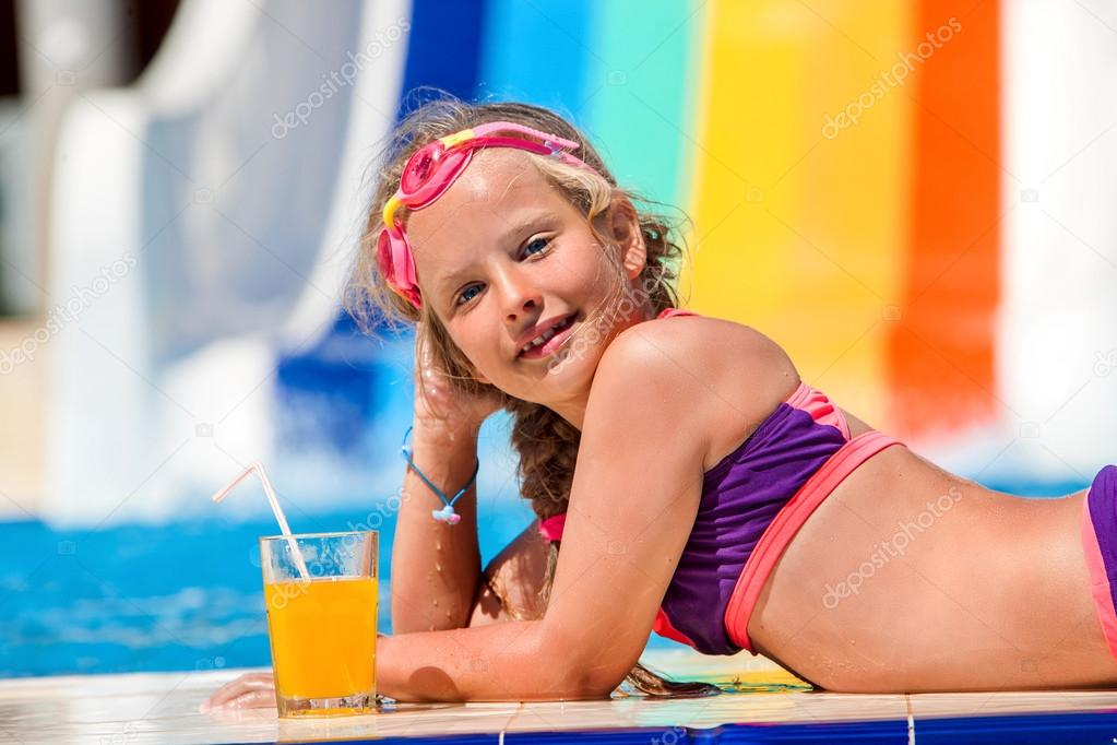 Child on water slide at aquapark drinking cold squeezed orange juice.