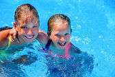Two different ages children swim in swimming pool.