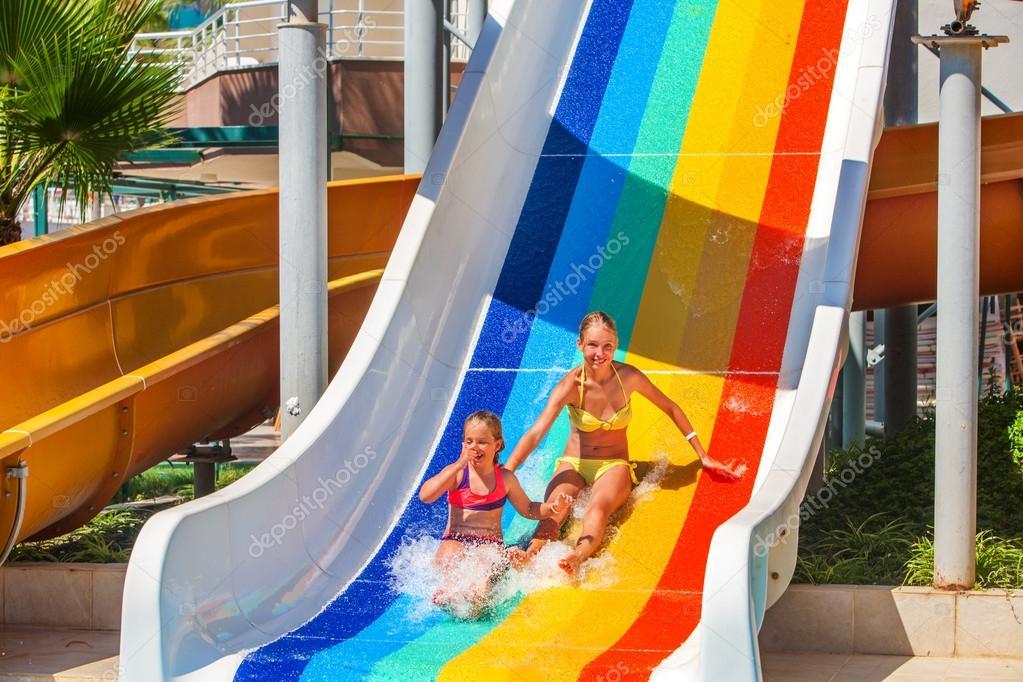 children at aquapark slide down water slides.