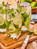Photo On wooden boards is glasses with mohito and knife.