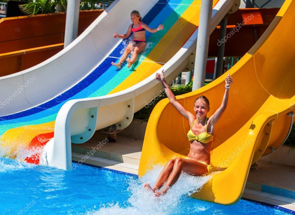 Children nice girl on water slide at aquapark.