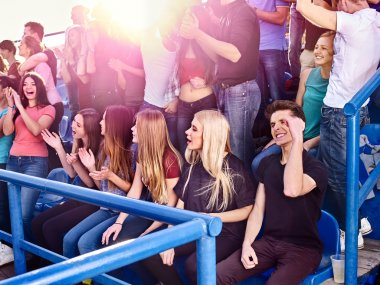 Sport olympiad fans singing on tribunes.