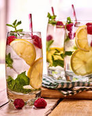 Photo On wooden boards is glasses with raspberry mohito and lime.