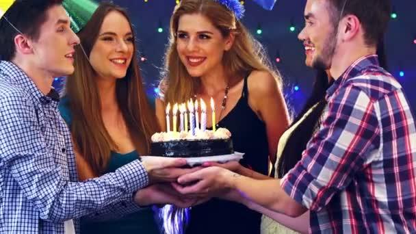 Dívka s kamarády oslavit narozeniny a sfouknout svíčky na cake.4k