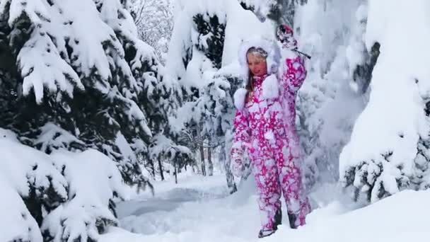 Child girl in winter playing in snow in park outdoor.