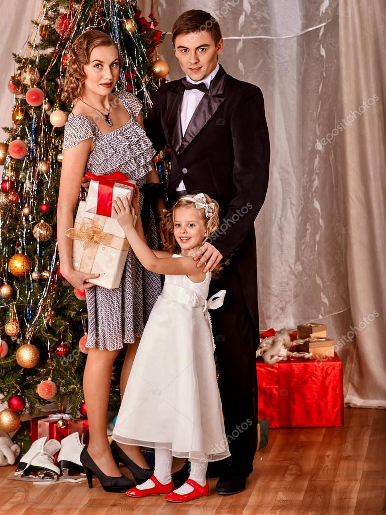 Family dressing Christmas tree. — Stock Photo © poznyakov #58344401
