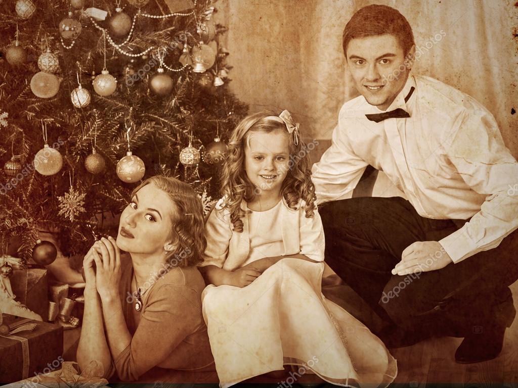 Family dressing Christmas tree. — Stock Photo © poznyakov #58940829
