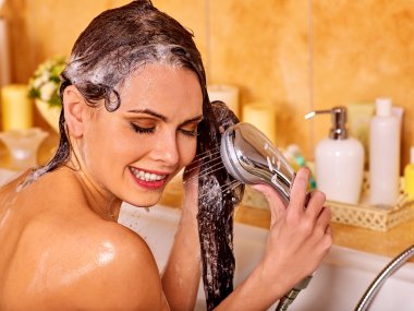 Woman washes her head at bathroom.