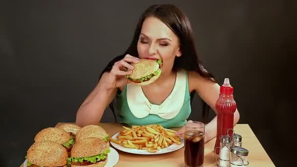 Woman eating sandwich and fast food