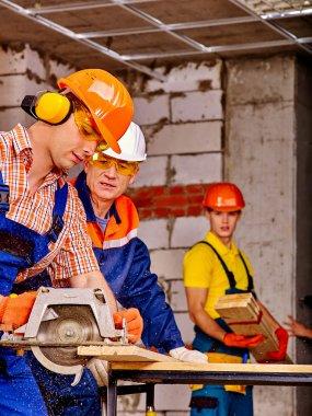 Happy group people  builders with circular saw working indoor. stock vector