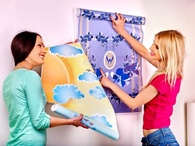 Women glues wallpapers at home.