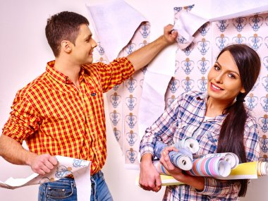 Family glues wallpaper at home.