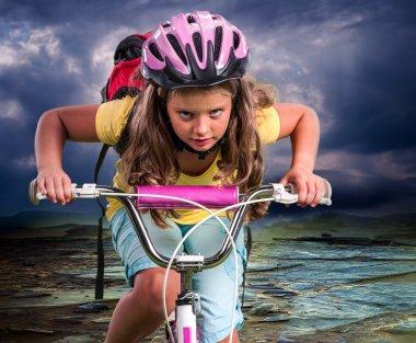 Child ride hard on bike to mountain.