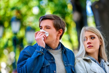 People with  cold blowing nose  handkerchief fall outdoor.