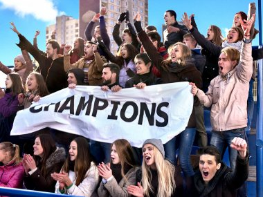 Sport fans holding champion banner on tribunes.