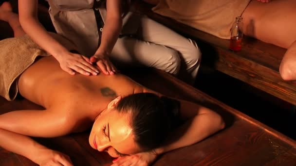 Pair of newlyweds getting massage in Thai spa on a wooden table.