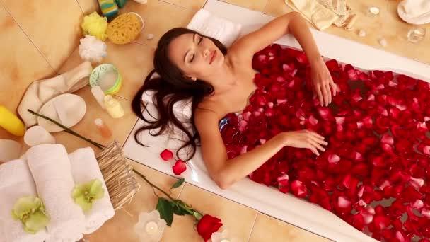 Dívka bere koupel s květy růží. Kamera se pohybuje od tváří k nohám. V pozadí hoří svíčky a koupelnové doplňky