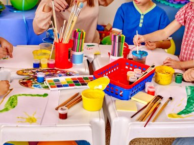 Kids hands holding colored paper and glue on table in kindergarten .