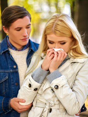 People with a cold blowing nose  handkerchief fall outdoor.