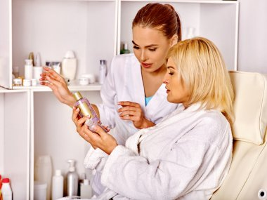 Woman 35-40 years old in spa salon with beautician.