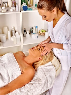 Woman middle-aged receiving  face massage in spa salon with beautician.