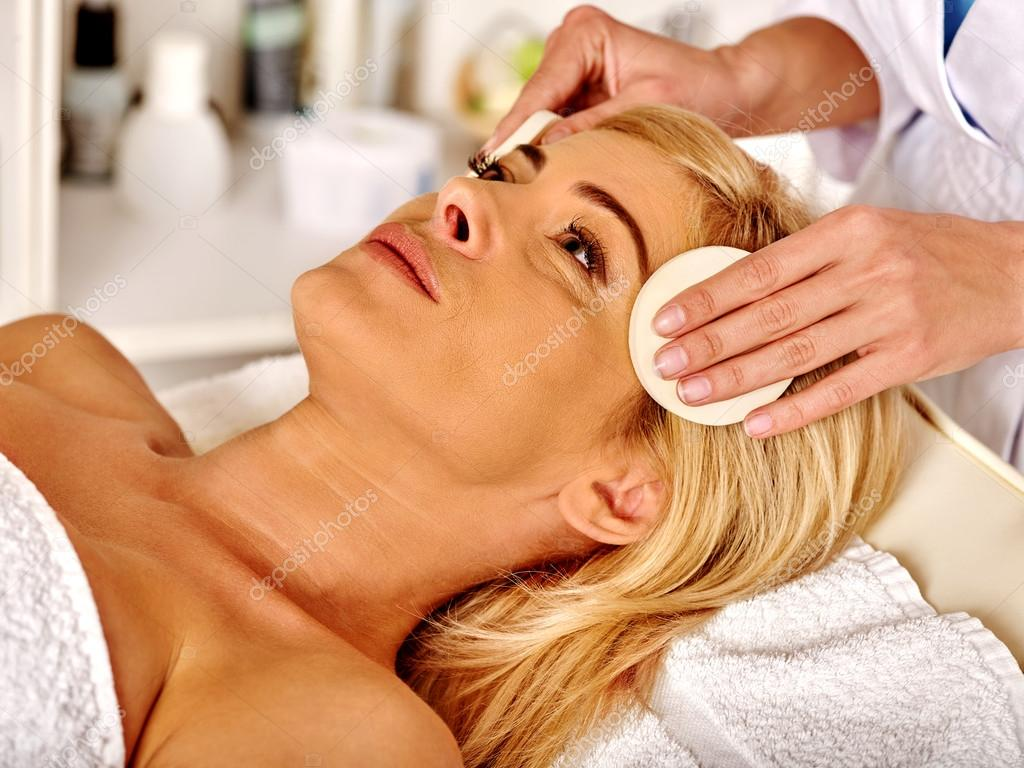 Woman middle-aged in spa salon and beautician cleanses face with sponge .