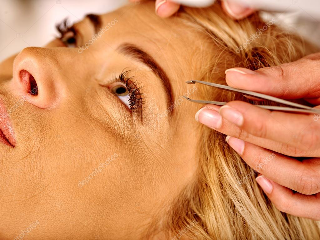 Woman middle-aged in spa salon. Tweezing eyebrow by beautician.
