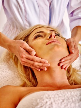 Woman middle-aged take face massage in spa salon.