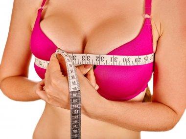 Girl wearing lingerie measures breast