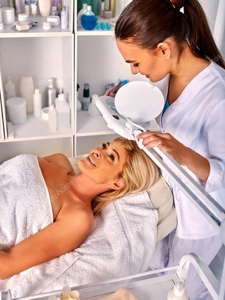 Woman in spa salon with cosmetic lamp