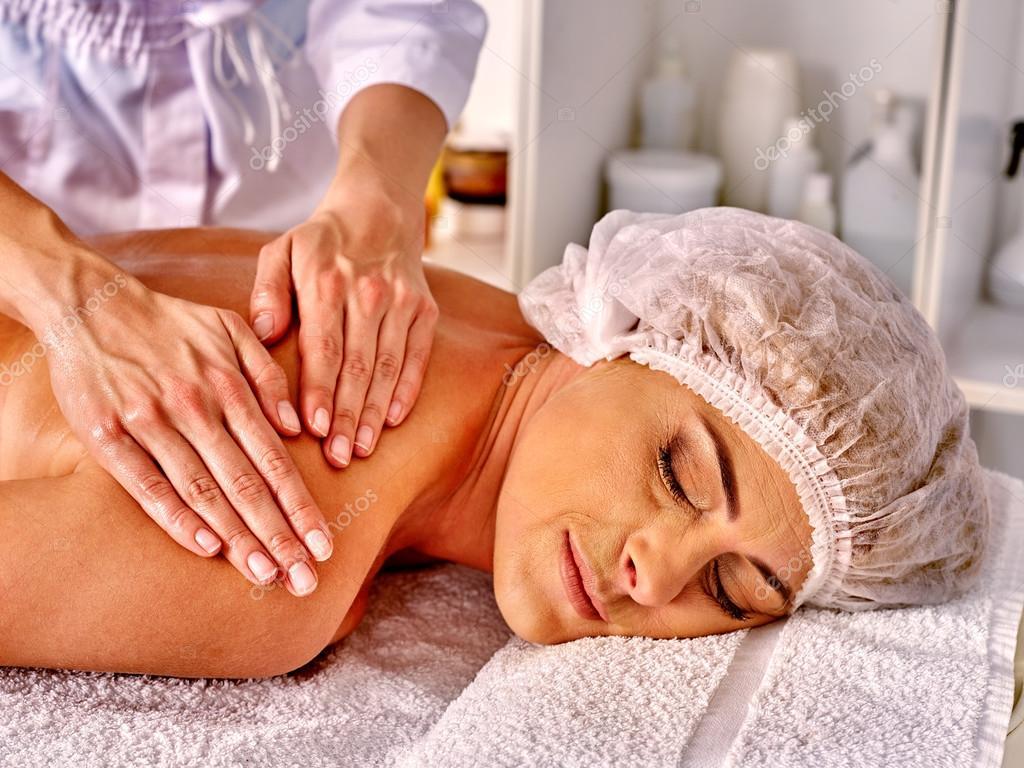 Woman take massage in spa salon