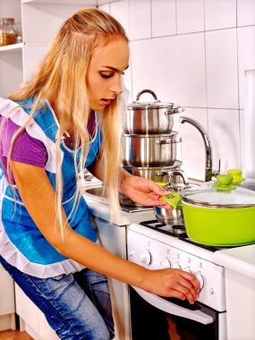 Housewife cooking at kitchen.