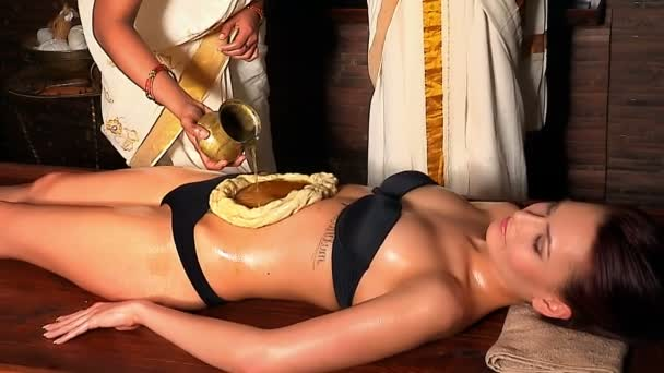 Woman having stomach Ayurveda spa treatment. Massage abdomen using pouring oil in  form of dough.