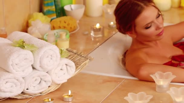 Young woman is relaxing with rose petals  bath in spa salon.