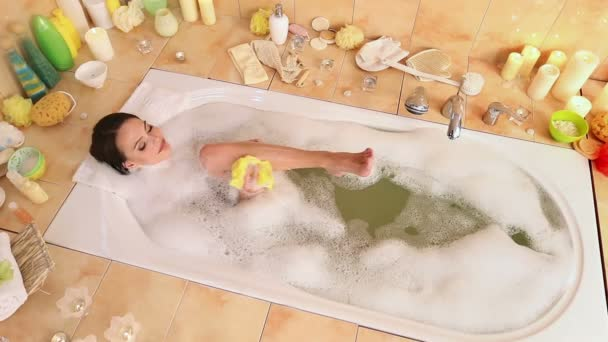 Woman taking  foam bath  and  chiropody by wisp of bast in her bathroom.