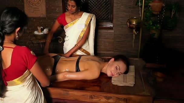 Žena dívka leží na břiše a mají lázeňské léčby. Dvě reálné indické masérky masáže rukou