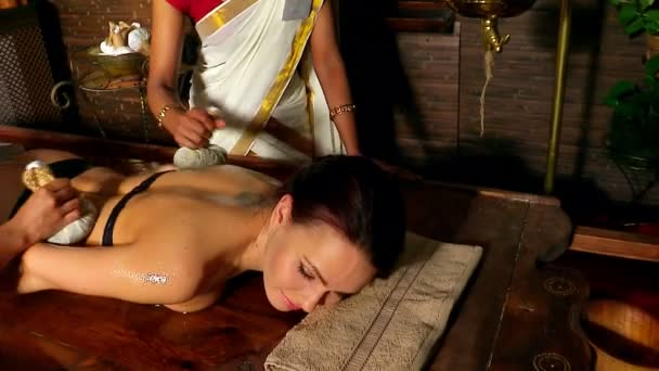 Woman having ayurvedic back massage with pouch of rice. One can see only hands  of Indian masseuses.