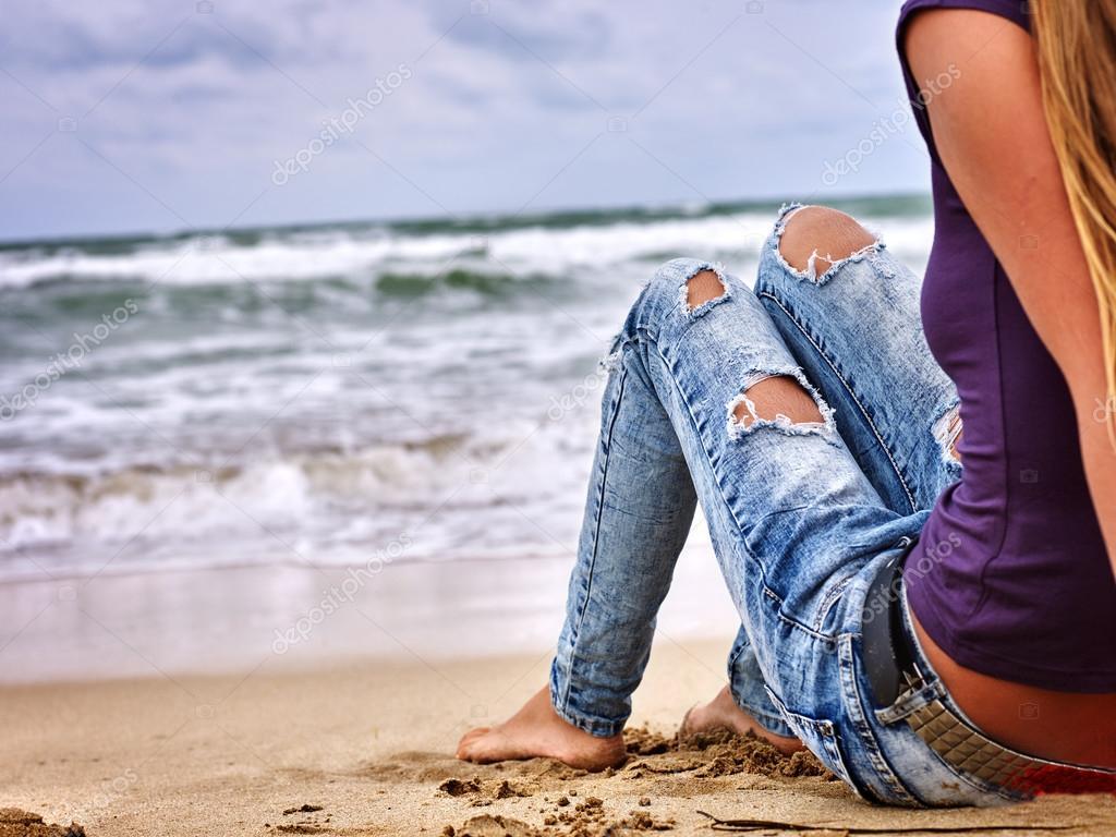 Legs of woman sitting on coast near ocean with waves. Hot dog leg selfie.