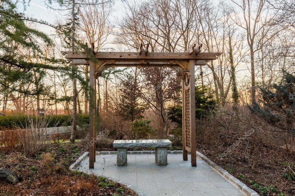 Pergolato in legno nella foresta con sedile in pietra u foto stock