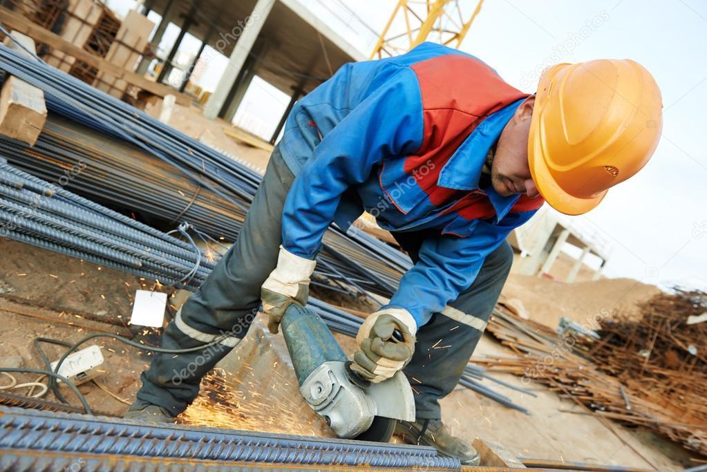 construction builder worker with grinder machine cutting metal reinforcement rebar rods at building site photo by kalinovsky