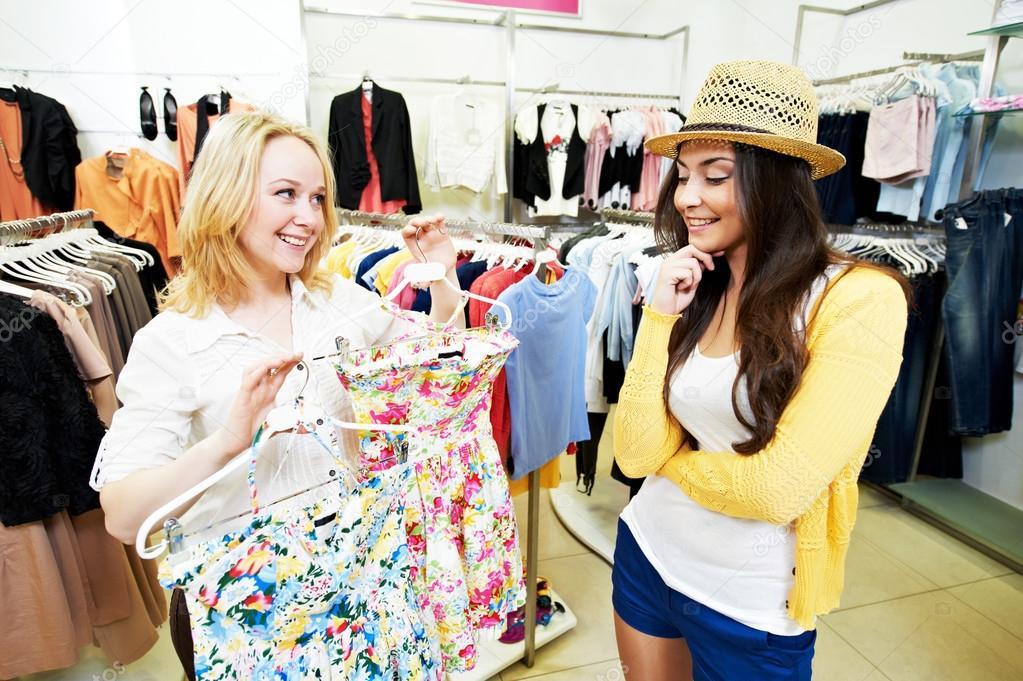 7dc41045f8 Dos mujeres jóvenes en comprar ropa de vestir — Foto de Stock
