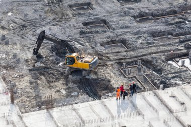 Working excavator with builders stand near