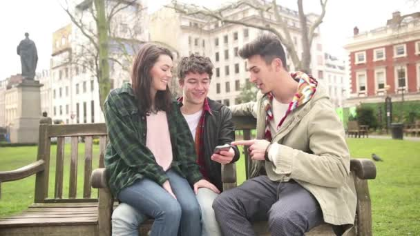 Three friends on a bench, talking and looking at smart phone