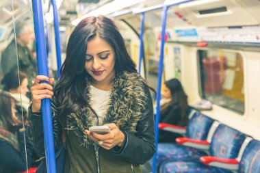 Young indian woman using smart phone in the tube