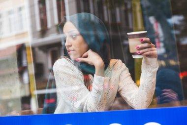 Muslim Woman Behind a Cafe Window