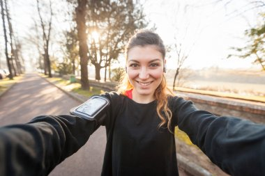 Young Sporty Woman Taking a Selfie at Park. She is Looking at Camera, that is the POV, Point of View, of the photo. She has a Smart Phone Holder on her Arm and Listen Music with Earphones. stock vector