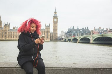 Beautiful woman listening music in London with Westminster on ba
