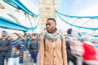 Man on Tower Bridge, London, with blurred people on background