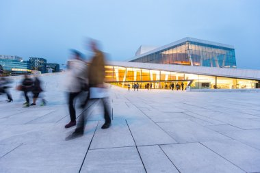 Blurred people in front of Opera House in Oslo at twilight.